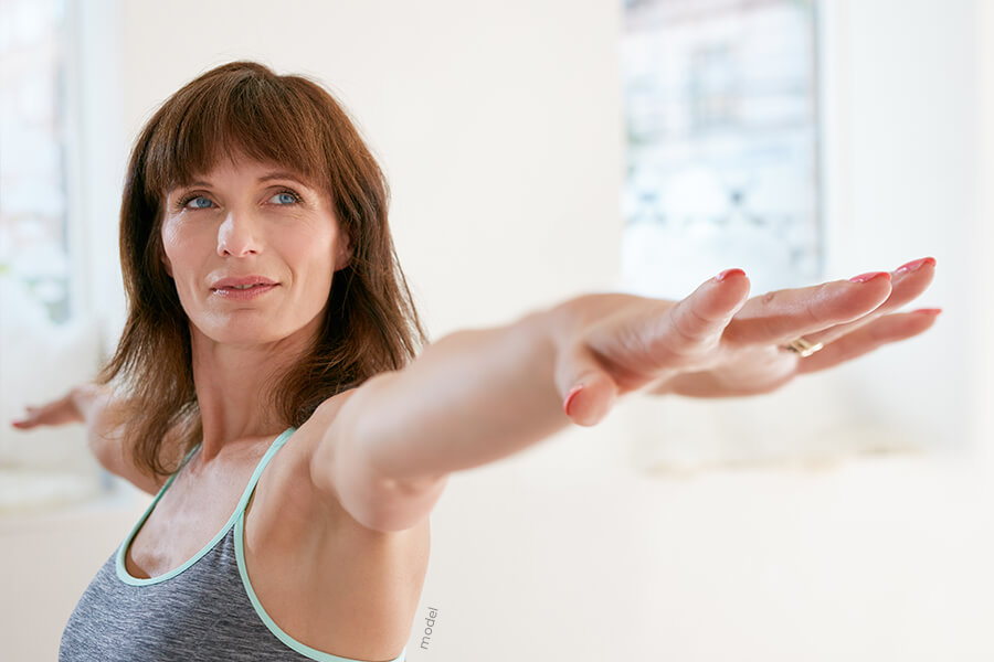 Attractive woman with arms up in yoga pose.